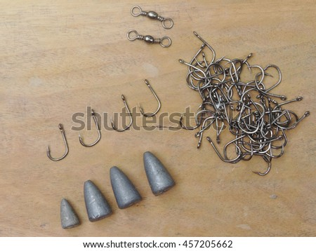 fish hook with lead disrupts fishing hook on wood background.           - stock photo
