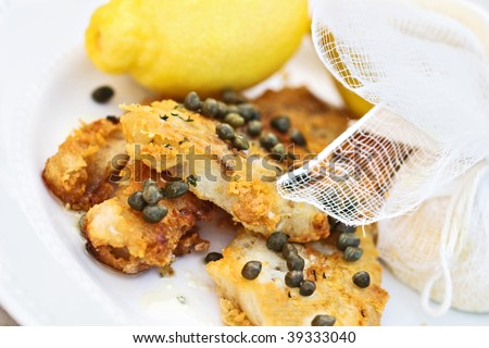 Fish in a buttery caper sauce served with lemons tied in cheesecloth