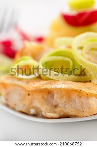 Fish in batter to plate on white table. - stock photo
