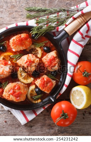 Fish in tomato sauce with olives and lemon in a frying pan. vertical top view - stock photo