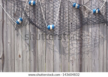 Fish net with blue and white floats hanging on a wooden fence - stock photo