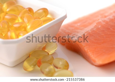 Fish oil capsules and salmon fillet slice - stock photo