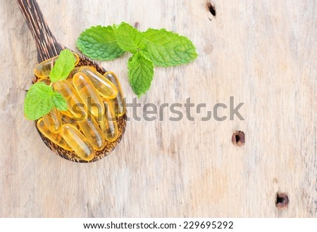 Fish oil capsules in a spoon. - stock photo