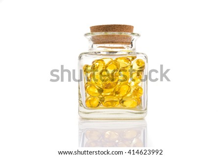 Fish oil capsules in translucent bottle on white background - stock photo
