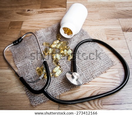 Fish oil omega 3 gel capsules  on wooden background - stock photo