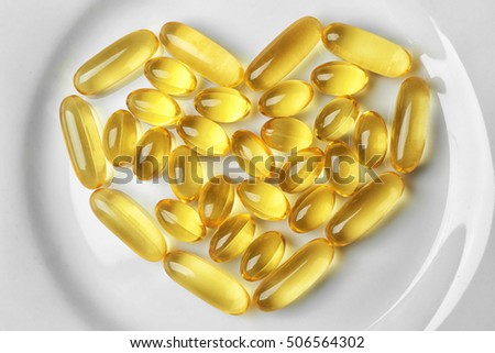 Fish oil pills in heart shape on plate, close up
