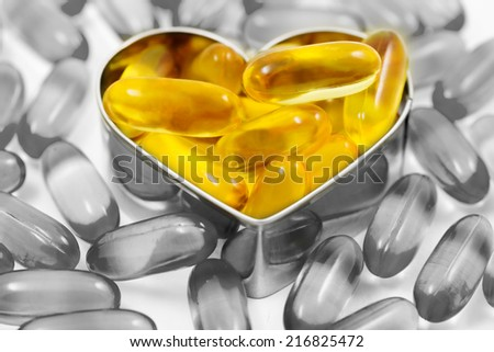 Fish oil pills on heart shape box among piles of fish oil pills black and white isolated on white background split tone - stock photo