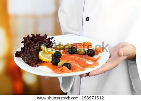 Fish on plate in cook hands on bright background
