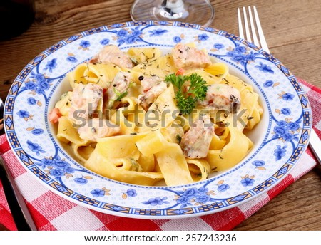 Fish salmon fillet with tagliatelle noodle, cream sauce, top view - stock photo