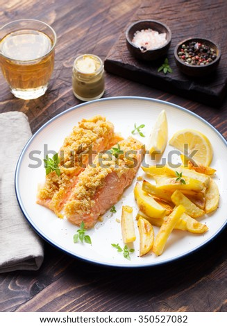 Fish salmon with crumple on top with baked potatoes and lemon slices on a wooden background