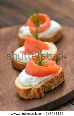 Fish sandwiches with salmon and dill on wooden cutting board - stock photo