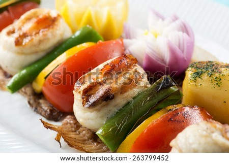 Fish skewers with fried potatoes - stock photo
