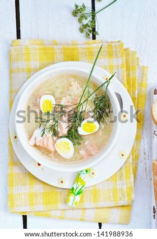fish soup with  quail eggs in to the wihte bowl - stock photo