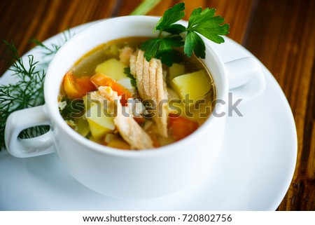 fish soup with vegetables in a plate on a wooden table