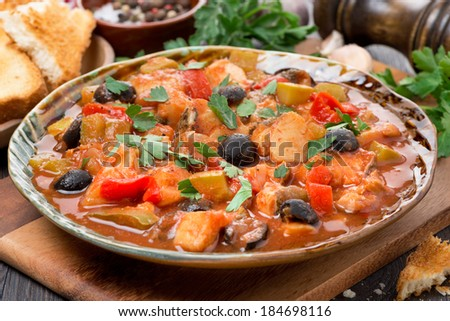 Fish stew with olives in tomato sauce on a plate, close-up, horizontal