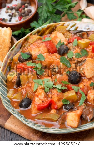Fish stew with olives in tomato sauce on a plate, vertical, close-up