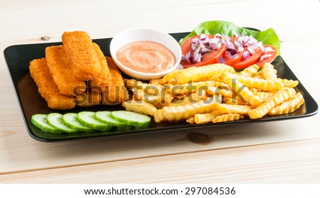 fish sticks with vegetables on a black plate - stock photo