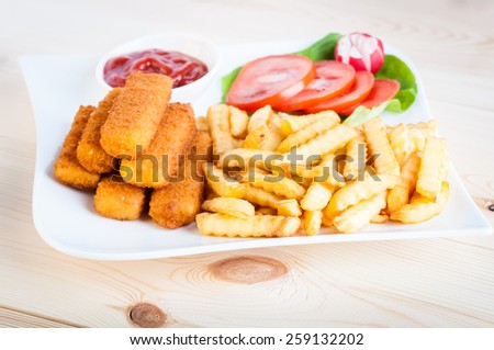 fish sticks with vegetables on a white plate - stock photo