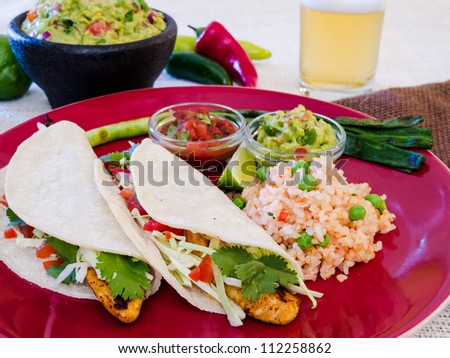 Fish Tacos with Guacamole and Rice: Seasoned grilled fish tacos in corn tortillas with salsa, cabbage, guacamole, lime, rice, and beer. - stock photo