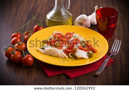 Fish with cherry tomatoes and olive. - stock photo