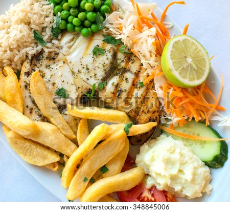 Fish with fried potato, rice and vegetables. - stock photo