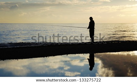 Fisher man with fishing rod silhouette on the beach at sunset - stock photo