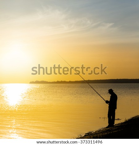 fisher silhouette on a river at the sunset