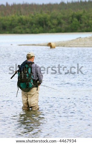 Fisherman and bear fishing for salmon, Katmai National Park, Alaska - stock photo