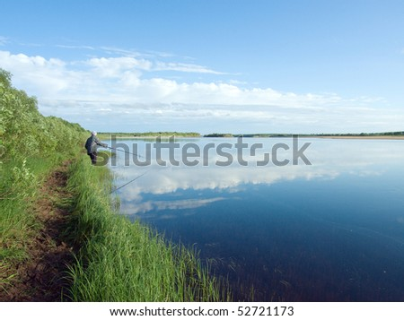 Fisherman angling on the river.fisher on a morning - stock photo