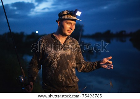 Fisherman at dusk preparing bait