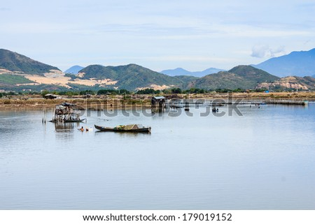 Fisherman at Tac river, Nha Trang, Vietnam. Nha Trang is well known for its beaches and scuba diving and has developed into a destination for international tourists. - stock photo