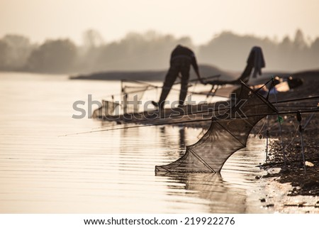 Fisherman at the border of the calm lake - stock photo
