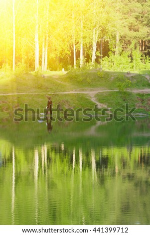 Fisherman at the forest lake in summer, sunny - stock photo