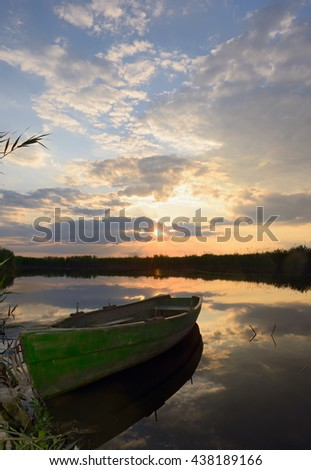 fisherman boat at sunset in summer time - stock photo