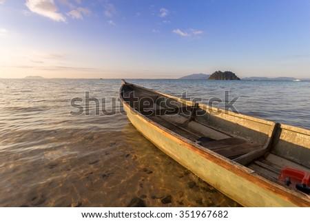 fisherman boat at the sea shore with crystal clear water during beautiful sunrise at the satang island, Sarawak Malaysia - stock photo
