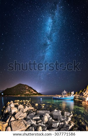 Fisherman boat in a little bay by night under the milky way - stock photo