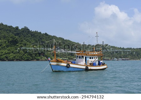 fisherman boat on green ocean with mountains in the background - stock photo