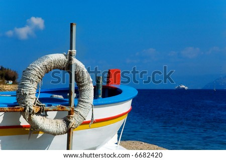 Fisherman boat overlooking Messina strait with sea and ship in the distance - stock photo