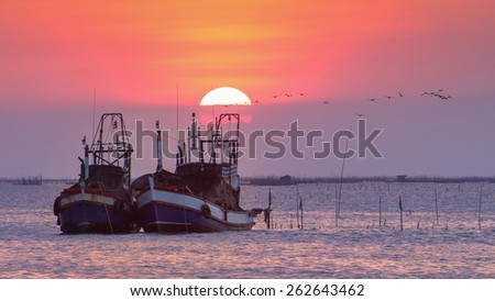 Fisherman boats in the sea with sunset and flock of birds in the background - stock photo