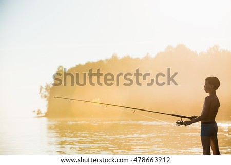 Fisherman boy stands in the water