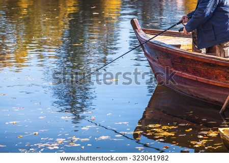 Fisherman catches a fish on a fishing rod with a big wooden boat bright autumn day - stock photo