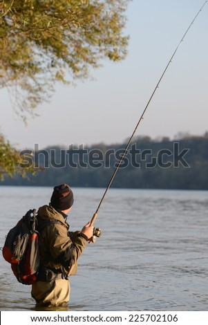 Fisherman catches fish in the river at spring