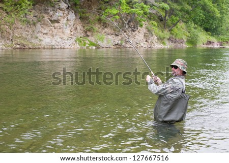 Fisherman catches of salmon in a mountain river.