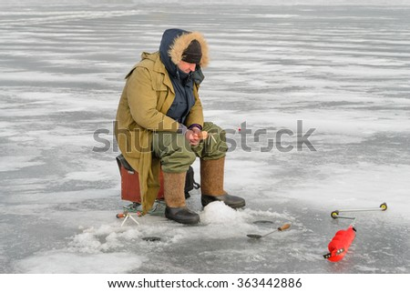 Fisherman catching a fish on ice fishing