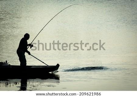 Fisherman Catching Fish on a Twilight Lake - stock photo