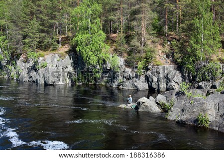 Fisherman catching fish on stream river water at the day - stock photo