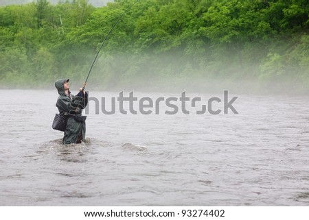 Fisherman caught a salmon. Rain. Fog. Morning.