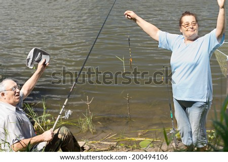 Fisherman celebrating the best catch of the day with his wife holding up a tiny tiddler in the hook with a theatrical flourish in a fun gesture - stock photo