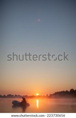 Fisherman enjoy a beautiful, golden, misty morning fishing on a lake. - stock photo