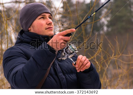 Fisherman fishes on a spinning winter
